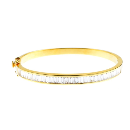 27 - A diamond hinged bangle. The baguette-cut diamond, channel-set line, to the plain half-bangle. Estim...