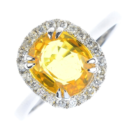 30 - A sapphire and diamond cluster ring. The cushion-shape yellow sapphire, with brilliant-cut diamond s...