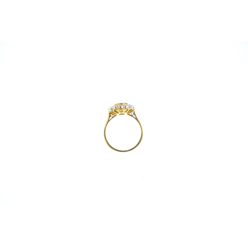 36 - An 18ct gold sapphire and diamond cluster ring. The oval-shape yellow sapphire, within a brilliant-c...