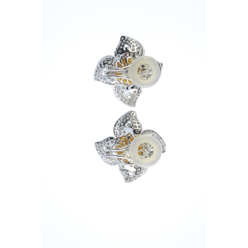 38 - A pair of diamond and cultured pearl floral earrings. Each designed as a golden cultured pearl, meas...