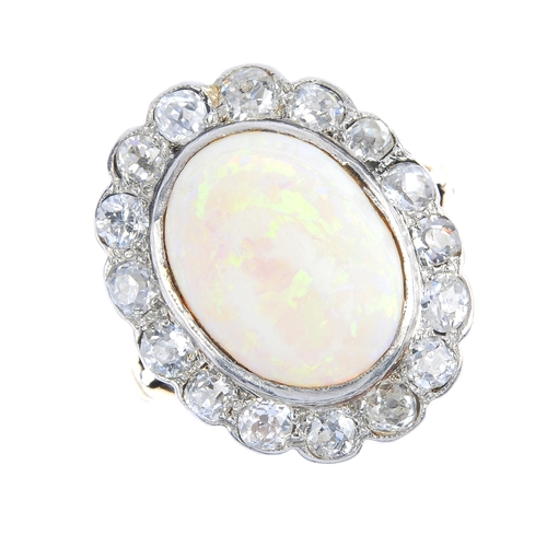 4 - An early 20th century platinum and 18ct gold, opal and diamond cluster ring. The oval opal cabochon,...
