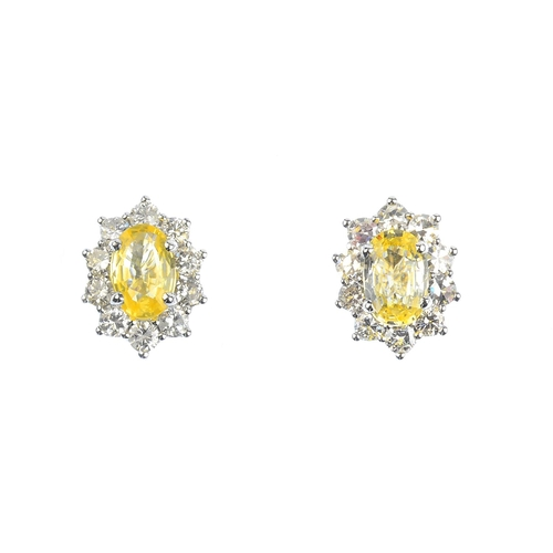 40 - A pair of sapphire and diamond cluster earrings. Each designed as an oval-shape yellow sapphire, wit...