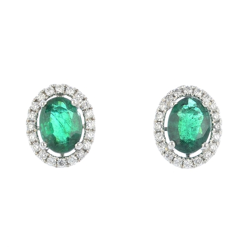 46 - A pair of emerald and diamond cluster earrings. Each designed as an oval-shape emerald, with brillia...