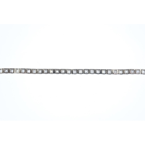 47 - A diamond bracelet. The baguette-cut diamond articulated line, within a channel setting. Estimated t...