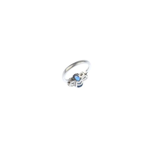 48 - A platinum sapphire and diamond three-stone ring. The oval-shape sapphire, with brilliant-cut diamon...
