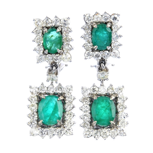 49 - A pair of emerald and diamond earrings. Each designed as an oval-shape emerald and brilliant-cut dia...
