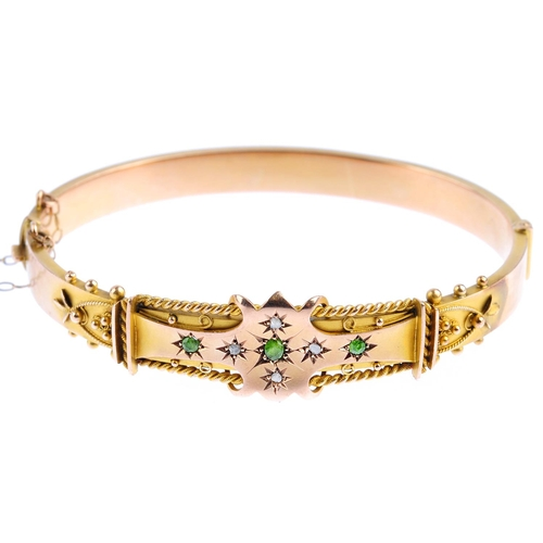 6 - An Edwardian 9ct gold demantoid garnet and diamond hinged bangle. The circular-shape demantoid garne...