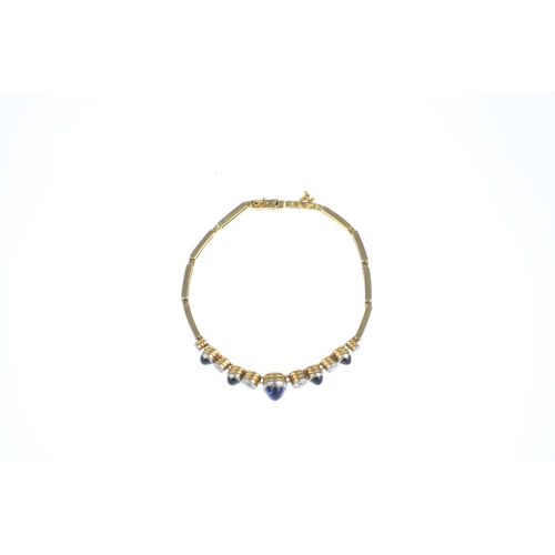 61 - An early 20th century platinum and gold sapphire and diamond bracelet. The oval sapphire collet with...