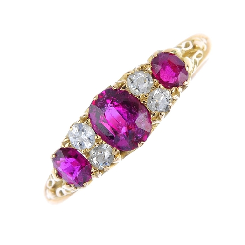 7 - An early 20th century 18ct gold ruby three-stone and diamond ring. The graduated oval-shape ruby lin...