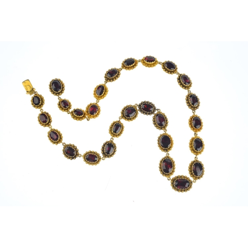 73 - A late Victorian garnet necklace. Comprising a graduated series of oval-shape garnet links, each wit...