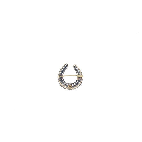76 - A late Victorian silver and gold diamond horseshoe brooch. Designed as two graduated old-cut diamond...