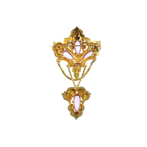 81 - An early Victorian gold topaz brooch. Of openwork design, the pear and oval-shape pink topaz quatref...