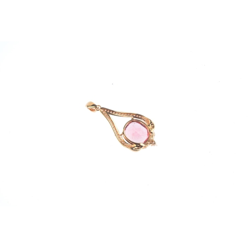 84 - A tourmaline and diamond pendant. Of openwork design, the oval-shape pinkish orange tourmaline, with...
