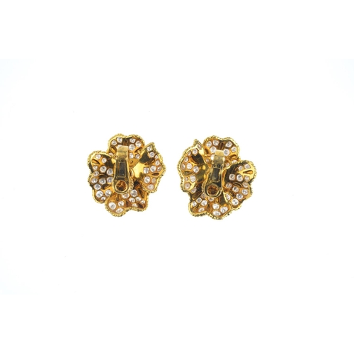87 - A pair of 1970s ruby and diamond floral earrings. Each designed as an oval ruby cabochon cluster, to...