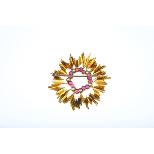 92 - A mid 20th century ruby and diamond brooch. The circular-shape ruby and brilliant-cut diamond irregu...