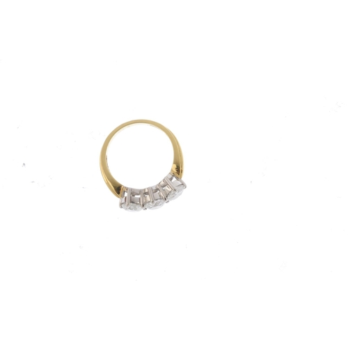 93 - An 18ct gold diamond three-stone ring. The brilliant-cut diamond line, with grooved shoulders. Total...
