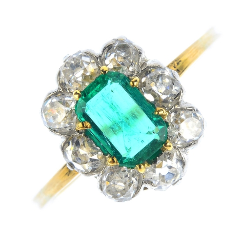 97 - An emerald and diamond cluster ring. The rectangular-shape emerald, with old-cut diamond surround. E...