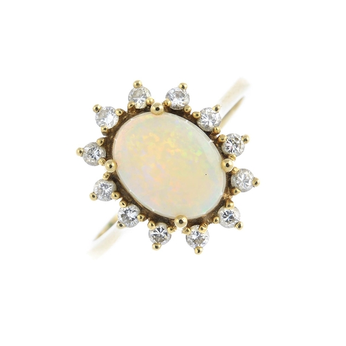 12 - A 9ct gold opal and diamond cluster ring. The oval opal cabochon, with brilliant-cut diamond surroun...