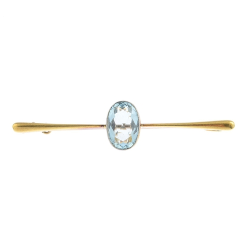 13 - An early 20th century 15ct gold aquamarine bar brooch. The oval-shape aquamarine collet, with tapere...