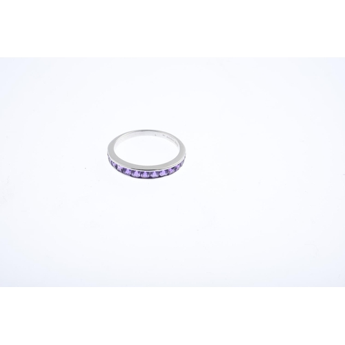 14 - An 18ct gold amethyst half eternity ring. Designed as a square-shape amethyst graduated line, within...