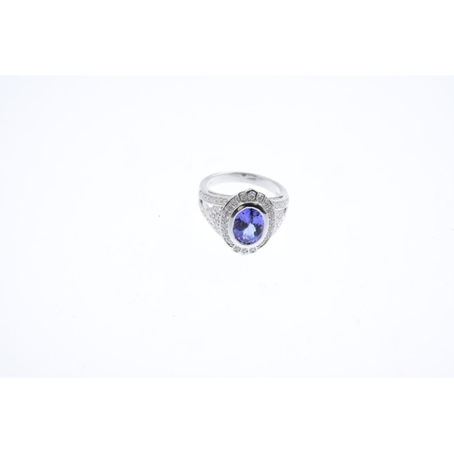 4 - A tanzanite and diamond dress ring. The oval-shape tanzanite and brilliant-cut diamond cluster, with...