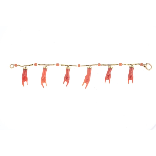 47 - A coral figa bracelet. Designed as a series of coral figa hands, suspended from a snake-link chain, ...