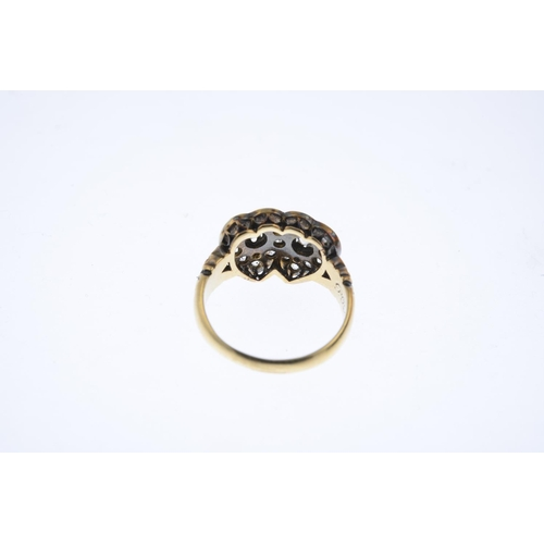 22 - A late Victorian 18ct gold diamond ring. Designed as two old-cut diamond overlapping hearts, with sc...