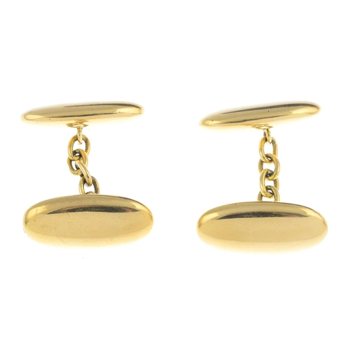 34 - A pair of early 20th century 18ct gold cufflinks. Each designed as a hollow oval, with similarly-des...