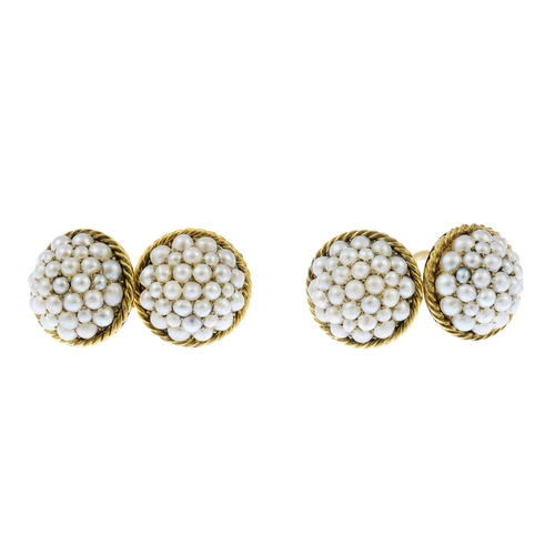 35 - A pair of split pearl cufflinks. Each designed as a pave-set split pearl dome, with rope-twist surro...