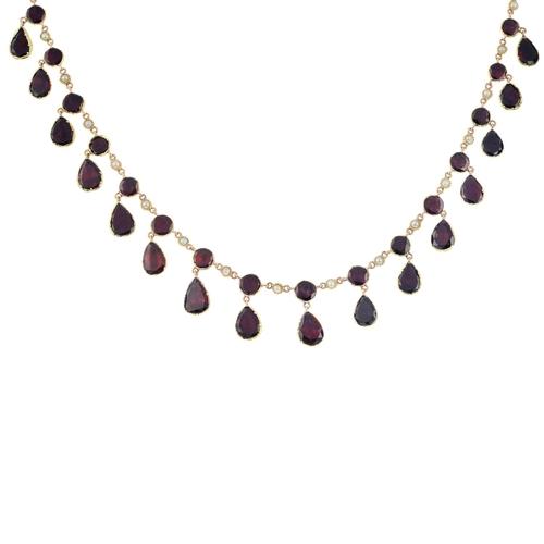 54 - A gold foil-back garnet and split pearl necklace. Comprising a pear-shape foil-back garnet fringe, s...