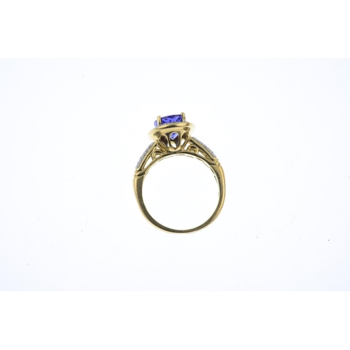 9 - A tanzanite and diamond cluster ring. The oval-shape tanzanite, with brilliant-cut diamond surround ...