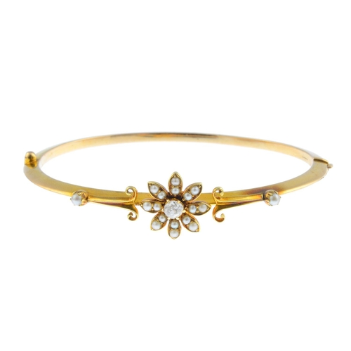20 - An early 20th century 15ct gold, split pearl and diamond hinged bangle. The old-cut diamond and spli...