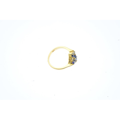 22 - A sapphire and diamond cluster ring. Of kite-shape outline, the cushion and circular-shape sapphire ...