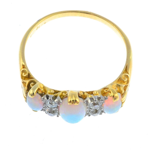 25 - An early 20th century 18ct gold and platinum, opal and diamond ring. The graduated oval opal cabocho...