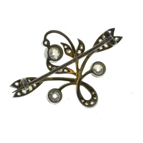 38 - An Art Nouveau silver and gold diamond floral brooch. The old-cut diamond collet buds, to the simila...