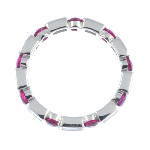 45 - A ruby and diamond full eternity ring. Designed as a series of baguette-cut diamond collets, with ci...