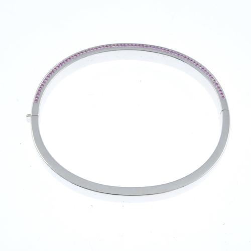 55 - An 18ct gold diamond and sapphire hinged bangle. The pave-set diamond panel, with similarly-set pink...