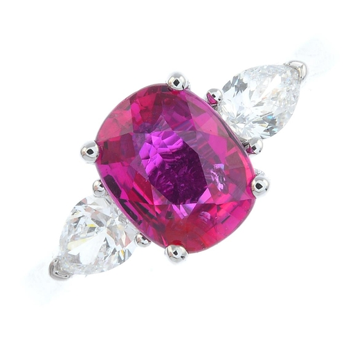 56 - An 18ct gold ruby and diamond three-stone ring. The cushion-shape ruby, with pear-shape diamond side...