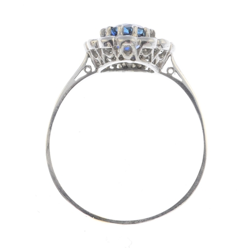 1 - A Sri Lankan sapphire and diamond cluster ring. The circular-shape sapphire, with old-cut diamond su...