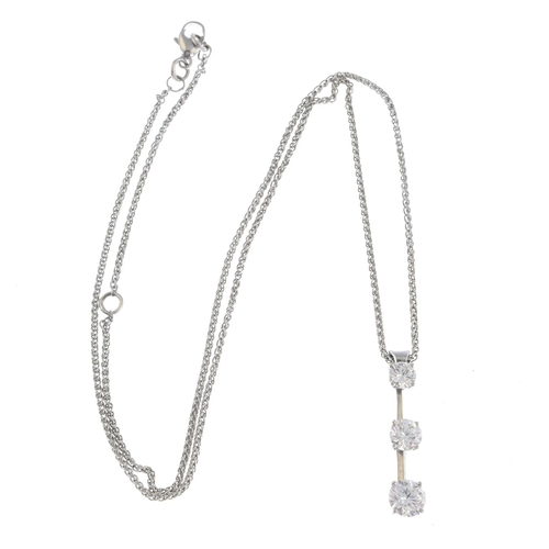 11 - A diamond three-stone pendant. The graduated brilliant-cut diamond line, with bar spacers, suspended...