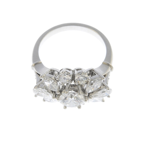 14 - A diamond cluster ring. The brilliant-cut diamond, with vari-cut diamond surround and brilliant-cut ...