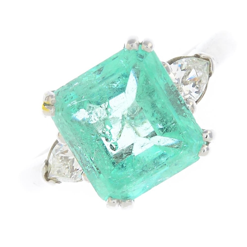 2 - An 18ct gold emerald and diamond three-stone ring. The rectangular-shape emerald, with pear-shape di...