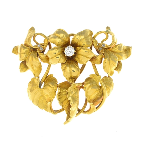 23 - An early 20th century 18ct gold diamond brooch. Comprising three old-cut diamond accent flowers on s...