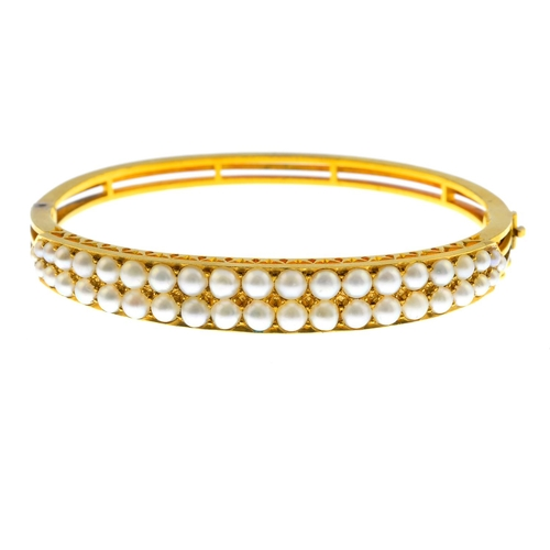 31 - An early 20th century gold split pearl bangle. Designed as two split pearl lines, hinged to the open...