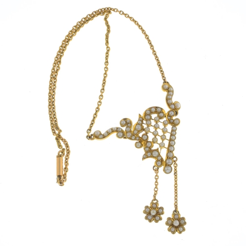 33 - An early 20th century 15ct gold seed pearl necklace. The split pearl stylised harp panel, suspending...