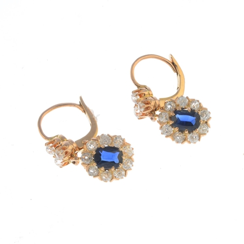 34 - A pair of sapphire and diamond earrings. Each designed as an oval-shape sapphire and old-cut diamond...