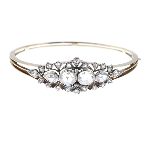 39 - An Edwardian gold and silver, diamond hinged bangle. Of openwork design, the graduated rose-cut diam...