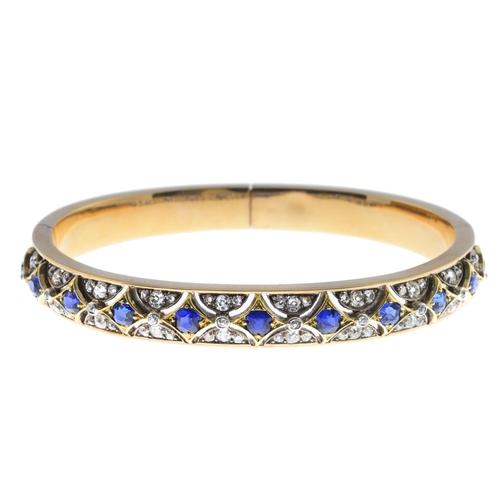 41 - A late Victorian gold sapphire and diamond hinged bangle. Of geometric design, the cushion-shape sap...