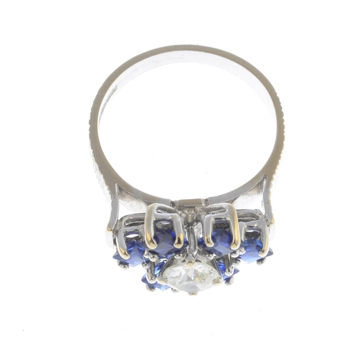 43 - A 1970s 18ct gold sapphire and diamond floral cluster ring. The circular-cut diamond, with square-sh...