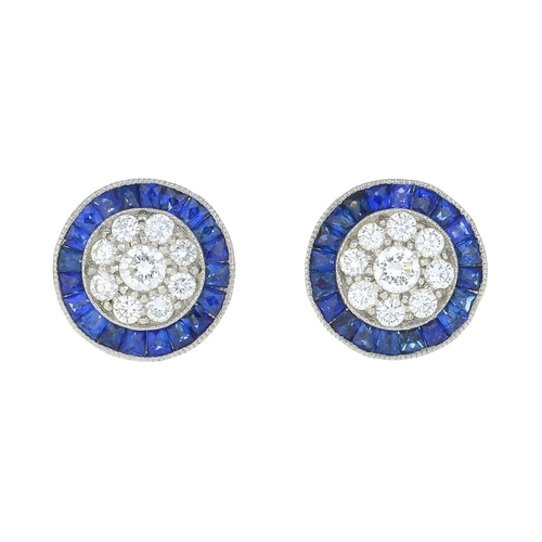 44 - A pair of diamond and sapphire earrings. Each designed as a brilliant-cut diamond cluster, with cali...
